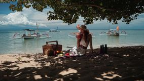 Young woman on beach picnic drinks juice under tree stock video footage
