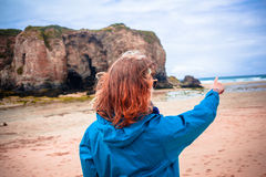 Young woman on beach is pointing Royalty Free Stock Images