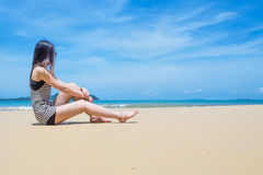 Young woman on the beach. Young woman relaxing on the beach in bule sky royalty free stock images