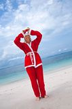 Young woman on the beach in santa's costume Royalty Free Stock Photo