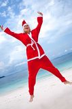 Young woman on the beach in santa's costume Royalty Free Stock Images