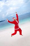 Young woman on the beach in santa's costume Stock Image