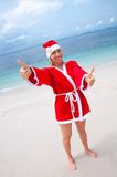 Young woman on the beach in santa's costume Royalty Free Stock Image