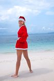 Young woman on the beach in santa's costume Stock Photography