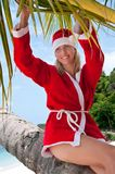 Young woman on the beach in santa's costume Royalty Free Stock Photography