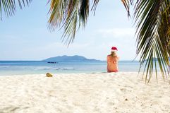 Young woman on the beach in santa's hat Royalty Free Stock Image