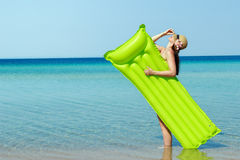 Young woman on the beach. A young woman on the beach with a straw hat and a green water matress Stock Photography