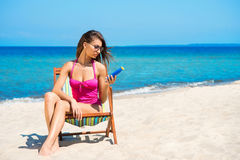 A young woman on the beach with a suntan bottle Stock Image