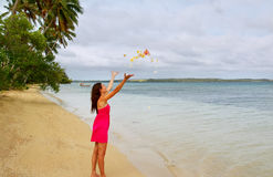 Young woman on a beach throwing flowers in the air Royalty Free Stock Photography