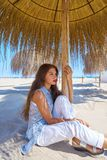 Young woman in a beach under parasol. Young latin woman in a beach under parasol at summer Stock Photos