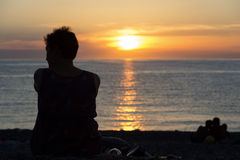 Young woman on the beach, watching the sunset Stock Photo