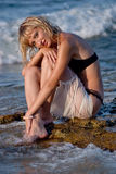 Young woman at beach in water. Beautiful blond girl in black bikini sitting on the stone near water at the beach in summer royalty free stock photo