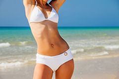 Young woman on the beach. Young woman in white bikini standing on the beach stock images