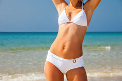 Young woman on the beach. Young woman in white bikini standing on the beach royalty free stock photos