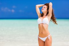 Young woman on the beach. Young woman in white bikini standing on the ocean beach stock image