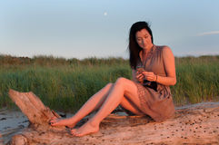 Young Woman Beachside Texting on Mobile Phone Royalty Free Stock Photo