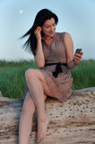 Young Woman Beachside Texting on Mobile Phone. A young woman in a sundress sits upon a driftwood log composing a text message on a dunegrass-lined beachfront royalty free stock photo