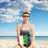 Young woman in beachwear with Italian flag on seashore. Young woman in beachwear with Italian flag on the seashore royalty free stock photos