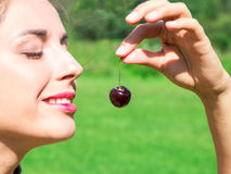 Young woman in beads made of fresh cherry holding cherry on open mouth with summer green forest background Stock Photography
