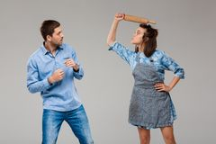 Young woman beating man with rolling pin over grey background. stock photos