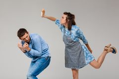 Young woman beating man with rolling pin over grey background. Stock Image