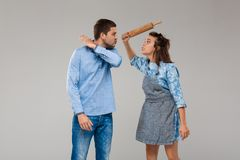 Young woman beating man with rolling pin over grey background. Royalty Free Stock Image