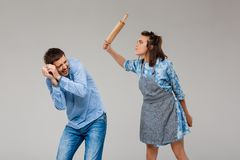 Young woman beating man with rolling pin over grey background. Royalty Free Stock Photography