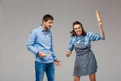 Young woman beating man with rolling pin over grey background. Stock Photo