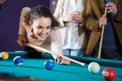 Young woman beats ball in billiards. Young smiling female beats ball in billiards Royalty Free Stock Images