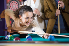 Young woman beats ball in billiards. Young smiling women beats ball in billiards Stock Photography