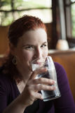 Young Woman with Beautiful Auburn Hair Drinking Water royalty free stock photos