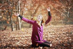 Young woman in beautiful autumn park, concept autumn. Girl, sitting in the woods, throws leaves in the air and smiles royalty free stock photo