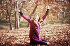 Young woman in beautiful autumn park, concept autumn. Girl, sitting in the woods, throws leaves in the air and smiles stock images