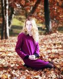 Young woman in beautiful autumn park, concept autumn. Girl sitting among the dry leaves in the woods stock photos