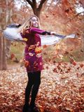 Young woman in beautiful autumn park, concept autumn. Girl, standing in the woods, makes a giravolta, throws leaves in the air and smiles royalty free stock image