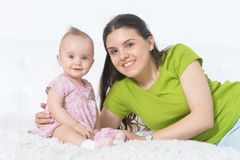 Young woman with  baby girl. Young woman with beautiful baby girl posing at home Stock Images