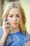 Young woman with beautiful blonde straight long hair in motion talking on the phone, solving disputes and conflicts.  stock photos
