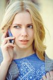 Young woman with beautiful blonde straight long hair in motion talking on the phone, solving disputes and conflicts.  stock image