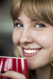 Young Woman with Beautiful Blue Eyes. Portrait of a young woman staring straight ahead into the camera holding a cup of coffee Stock Images