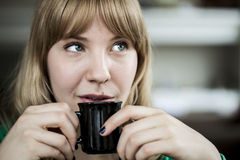 Young Woman with Beautiful Blue Eyes. Portrait of a young woman staring straight ahead into the camera holding a cup of coffee Royalty Free Stock Image