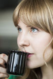 Young Woman with Beautiful Blue Eyes. Portrait of a young woman staring straight ahead into the camera holding a cup of coffee Royalty Free Stock Images