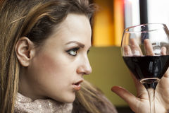 Young Woman with Beautiful Blue Eyes Drinking Red Wine Stock Image