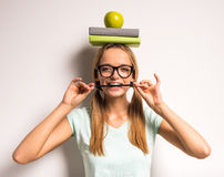 Young woman. Beautiful young woman with a books and apple on her head Stock Images