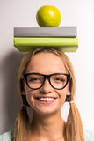 Young woman. Beautiful young woman with a books and apple on her head Royalty Free Stock Photo