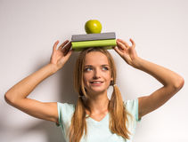 Young woman. Beautiful young woman with a books and apple on her head Stock Image