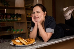 Young woman with beautiful breasts on the bar with pies royalty free stock photo
