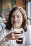 Young Woman with Beautiful Brown Eyes Drinking a Pint of Stout Stock Images