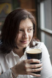 Young Woman with Beautiful Brown Eyes Drinking a Pint of Stout Stock Image