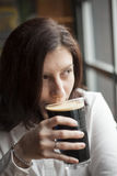 Young Woman with Beautiful Brown Eyes Drinking a Pint of Stout royalty free stock photography