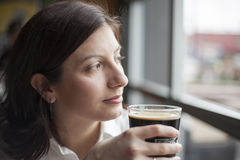 Young Woman with Beautiful Brown Eyes Drinking a Pint of Stout stock photo